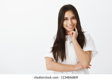 Waist-up portrait of positive friendly-looking girlfriend with dark hair, touching chin with fingers and smiling joyfully, having creative idea or thought, planning perfect date over gray background
