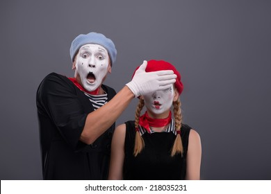 Waist-up portrait of scared mime couple, male mime looking at the camera with consternation on his face and closing eyes of his girlfriend isolated on grey background with copy place