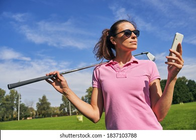 Waist-up portrait of a serious sportswoman with a golf club staring at her mobile phone