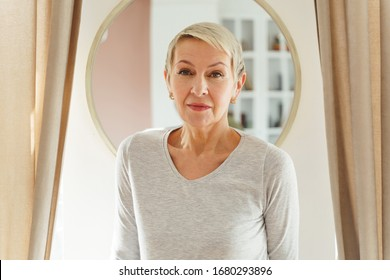 Waist-up portrait of a serious woman in a v-neck jumper staring in front of her