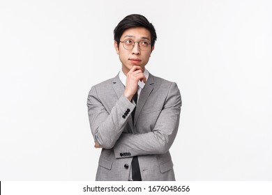 Waist-up portrait of smart and creative young asian male entrepreneur in grey suit, making plan, hold hand on chin and looking up thoughtful, thinking over project, standing white background