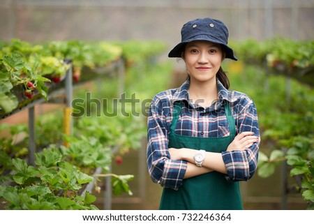 d6644eda853f6 Waist-up portrait of smiling Asian gardener wearing apron and bucket hat  standing at modern