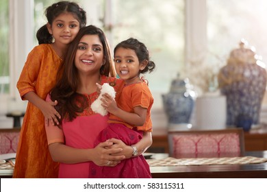 Waist-up portrait of smiling family: pretty woman with little daughters standing in living room with elements of traditional Indian decor and looking at camera