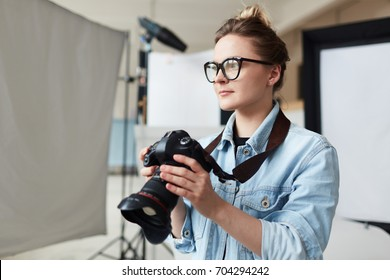 Waist-up portrait of talented young photographer in eyeglasses holding professional camera in hands and looking away pensively, interior of spacious photostudio on background