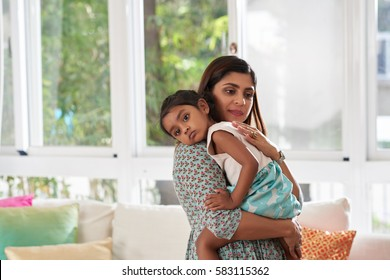 Waist-up portrait of thoughtful Indian woman holding her daughter in arms and patting her on back while standing against panoramic window
