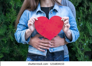 Waist-up portrait of two charming people hugging each other and holding big red paper heart. Relationship, valentine and love concept. Blurred background