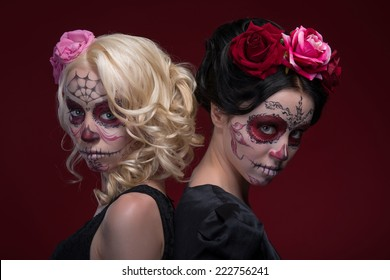 Waist-up portrait of two young girls standing back to back in black dresses with Calaveras makeup and roses in their hair eerily looking at the camera isolated on red background with copy place
