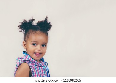 Waist-up portrait of wonderful baby girl showing tongue at camera. Little beautiful well-dressed kid with two ponytails posing inside. Childhood concept with copy space in right side