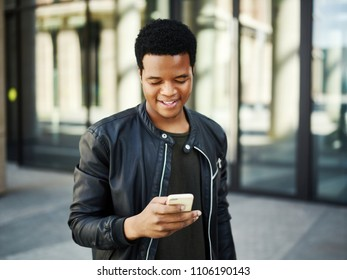 Waist-up portrait of young African American man text messaging on his smartphone while walking down city street