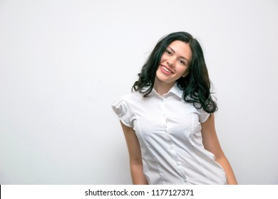 Waist-up portrait of young cheerful happy woman standing isolated on white background. Smiling well dressed model posing in studio. Copy space in left side