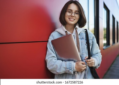 Waist-up portrait of young female programmer, IT or smm manager, want work outside in park during nice spring weather, standing with laptop lean red brick wall, smiling happy camera