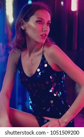 Waist-up portrait of young gorgeous woman with long brunette hair wearing elegant black sequin strap cami dress. Beautiful slender female model posing against glowing neon lights on background