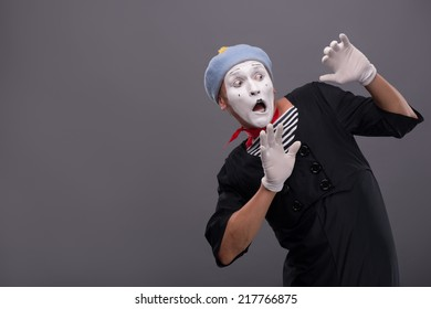 Waist-up portrait of young male mime confused breeding his hands showing that he is scared and frighten looking aside with wide opened mouth and eyes isolated on grey background with copy place