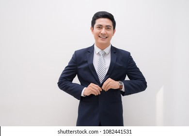 Waistup portrait of young smiling handsome businessman putting on suit jacket looking aside isolated on white