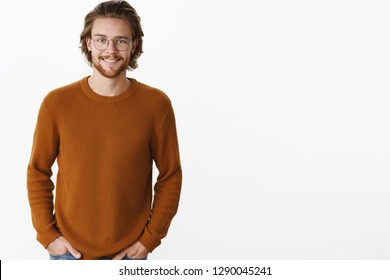 Waist-up shot of attractive pleasant bearded guy with earrings and long hair in glasses and warm sweater smiling friendly and happy at camera holding hands in pockets posing over gray background