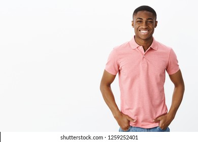 Waist-up shot of attractive positive and happy young african american male entrepreneur in pink polo shirt holding hands in pockets and smiling with self-assured delighted grin over white background