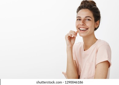 Waist-up shot of beautiful carefree woman listening hilarious joke smiling broadly looking amused and happy as laughing out loud attending stand-up show posing cheerful over gray background
