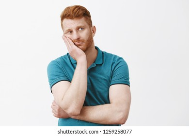 Waist-up shot of bored and tired gloomy redhead guy with bristle in green polo-shirt, leaning face on palm, staring right with exhausted and careless expression, having nothing to do over gray wall