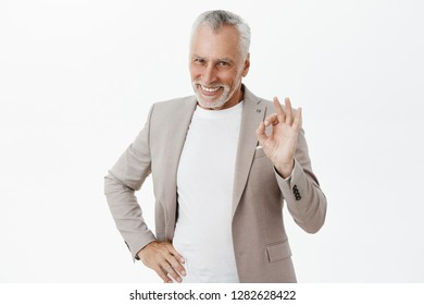 Waist-up shot of charming charismatic self-assured old bearded male having everything under control showing okay gesture smiling broadly holding hand on hip being assertive, confirming plan is perfect