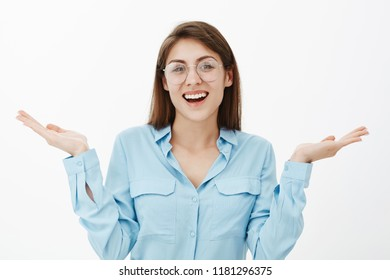 Waist-up shot of charming happy adult female in glasses and blue-collar shirt, shrugging with spread palms, smiling broadly, being indifferent to coworker problems, standing carefree with no worries
