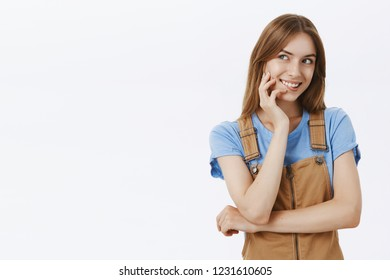 Waist-up shot of charming tender pretty feminine woman in brown overalls touching cheek gently gazing left with sensual flirty smile crossing one hand over chest standing cocky over gray background