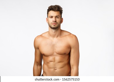 Waist-up shot confident good-looking, sexy young tanned man, athlete standing naked torso, squint, showing six-pack perfect body, train in gym, workout daily, lead active lifestyle. Bodybuilder promo