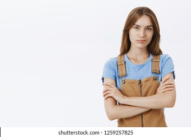 Waist-up shot of confident good-looking woman with good self-esteem holding hands crossed on chest in proud self-assured pose smirking as if being skillful and smart posing arrogant over gray wall