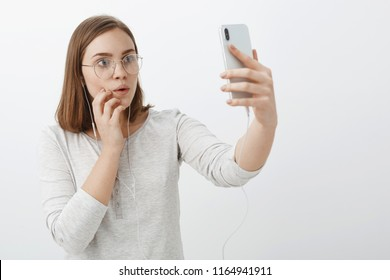 Waist-up shot of creative curious and entertained charming woman in glasses wearing earphones raising hand with smartphone gazing intrigued and interested at device screen watching amazing video