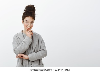 Waist-up shot of creative smart curly-haired female with bun hairstyle in trendy glasses and grey coat, biting finger and smiling with intrigued expression, being interested with something
