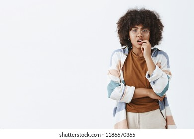 Waist-up shot of curious thoughtful and smart worried african american woman with afro hairstyle in transparent glasses biting fingernail and frowning while thinking how make hard choice