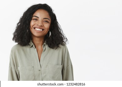 Waist-up shot of cute friendly-looking pleasant African American female friend with curly hairstyle in trendy blouse tilting head smiling joyfully and looking with warm tender expression at camera