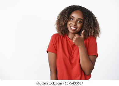 Waist-up shot of cute supportive african american girlfriend showing thumb up in like and approval tilting head and smiling broadly to cheer friend and encourage for excellent efforts over white wall