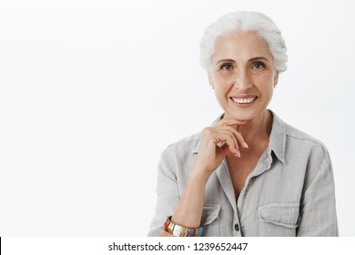 Waist-up shot of delighted relaxed and happy granny with white hair in shirt and bracelet holdign hand on chin and smiling with curious or interested expression thinking to accept interesting offer
