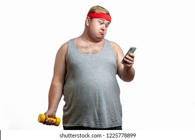 Waist-up shot of displeased gloomy obese male fatso in casual t-shirt, staring disappointed at camera, frowning and expressing dislike, looking at smartphone