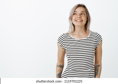 Waist-up shot of dreamy stylish woman with cool tattoos on arms, standing casually over gray background, smiling broadly while looking left with carefree expression, having fun and enjoying summer
