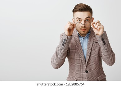 Waist-up shot of focused smart attractive caucasian young guy with trendy haircut taking off glasses staring amazed and intrigued at camera as if hearing exciting news over gray background