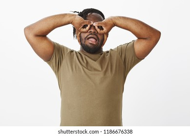 Waist-up shot of funny carefree african-american guy in olive t-shirt, holding hands over eyes and making faces, mimicking goggles or eyewear while fooling around over grey background