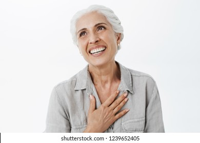 Waist-up shot of happy and delighted grateful charming old lady with white hair holding palm on chest in thankful gesture gazing dreamy and pleased at upper left corner cheerful have awesome family