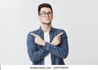 Waist-up shot of hesitant unsure attractive caucasian young man with bristle in glasses and blue shirt crossing hands on chest, pointing sideways as being doubtful what chose, looking right unsure