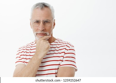 Waist-up shot of intelligent wise and creative old businessman in striped t-shirt standing in thoughtful pose rubbing beard and gazing interested and focused at camera thinking making impression
