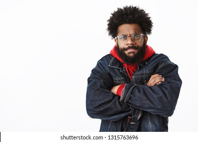 Waist-up shot of intense and bothered gloomy angry african american bearded man in glasses looking with judgement and disapproval frowning and sulking crossing arms over chest pissed