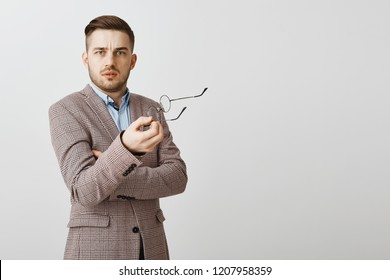 Waist-up shot of intense confused good-looking male entrepreneur in stylish jacket taking off glasses and gesturing with them near gray background staring questioned and perplexed at camera