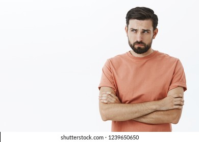Waist-up shot of lonely and gloomy displeased cute european guy in casual t-shirt crossing arms on chest frowning squinting looking left offended and sad standing gloomy and insulted over gray wall.