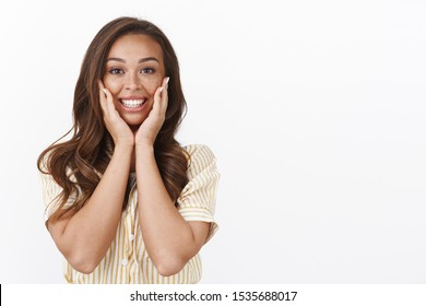 Waist-up shot pretty amazed brunette female put hands on cheeks and grinning astonished, look with adoration and joy, have happy moment, admiring fantastic scene, white background