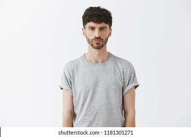Waist-up shot of serious-looking unemotional good-looking adult man in gray t-shirt looking at camera calm and strict, being snob and hard to impress standing over gray background