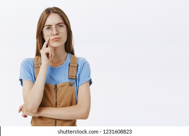Waist-up shot of thoughtful smart and intelligent young creative woman with brown hair in overalls and glasses squinting curiously looking determined and serious at camera while thinking