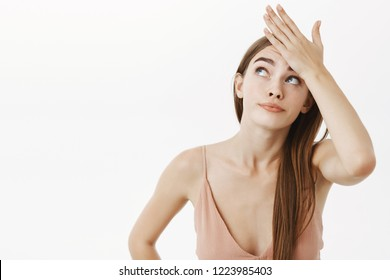 Waist-up shot of troubled beautiful caucasian female in beige evening dress holding hand on forehead and peeking up with intense bothered smirk being displeased with tiresome duties over gray wall