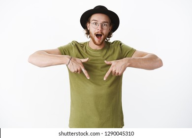 Waist-up shot of wondered and amazed handsome hipster guy feeling thrilled and curious as pointing down with raised index fingers asking question about awesome product being impressed