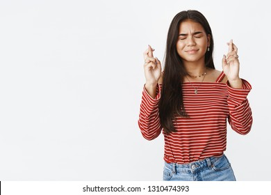Waist-up shot of worried cute indian teenage girl with dark long hair close eyes as praying, making wish with raised crossed fingers for good luck, anticipating miracle as waiting results