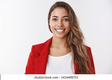 Waist-up successful lucky attractive european female wearing red jacket smiling white teeth staying positive, feeling upbeat getting promotion achieving goal, receiving compliment, looking satisfied